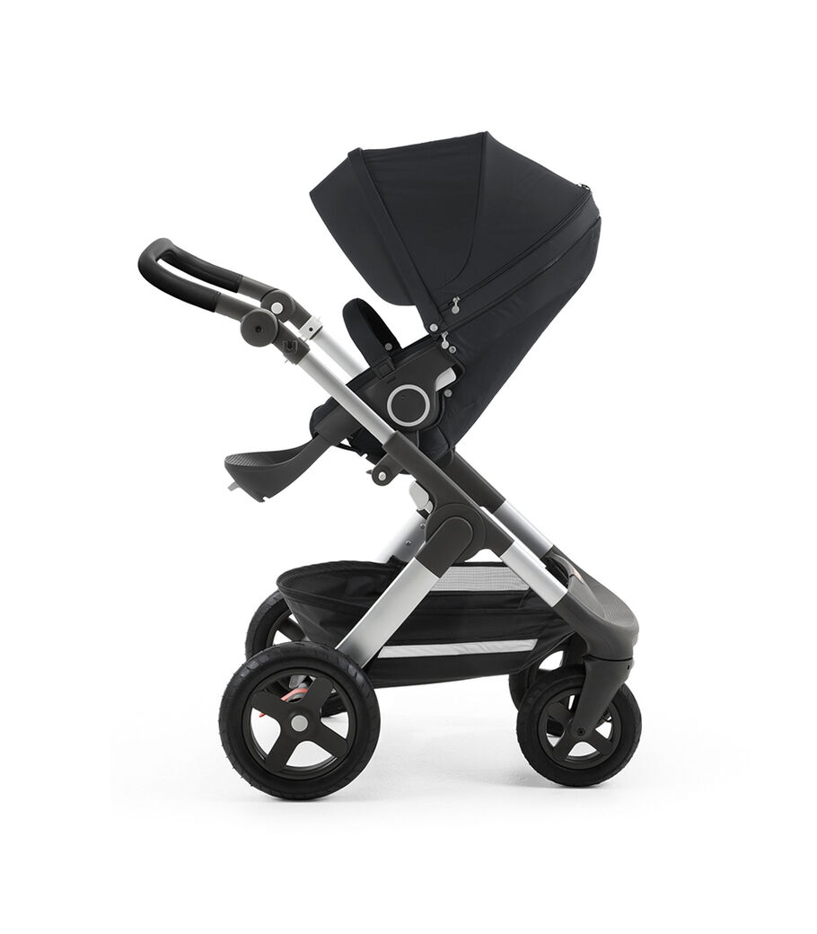 Stokke® Trailz™ with silver chassis and Stokke® Stroller Seat, Black. Leatherette Handle. Terrain Wheels.