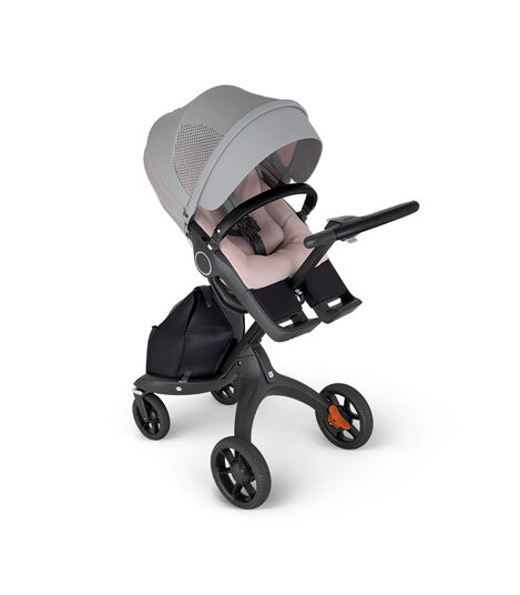 Stokke® Xplory® with Black Chassis and Leatherette Black handle. Stokke® Stroller Seat Athleisure Pink in angled view.