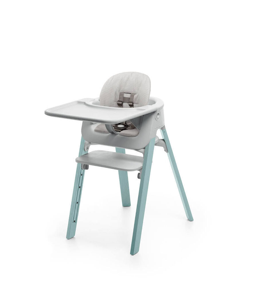 Stokke® Steps™ Aqua Blue with Accessories. Baby Set Light Grey. Baby Set Cushion Timeless Grey. Baby Set Tray Light Grey.