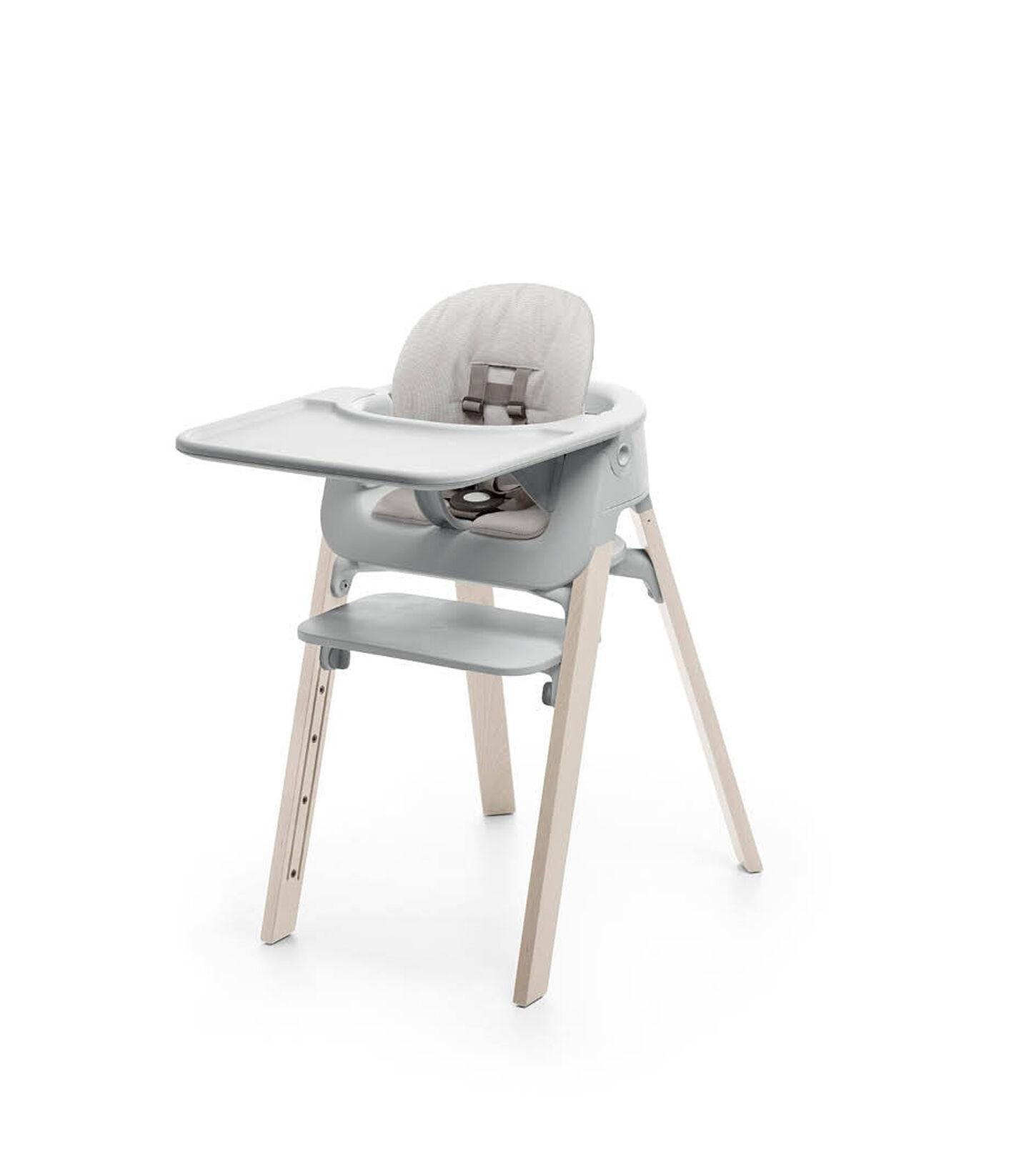 Stokke® Steps™ Whitewash with Accessories. Baby Set Light Grey. Baby Set Cushion Timeless Grey. Baby Set Tray Light Grey.