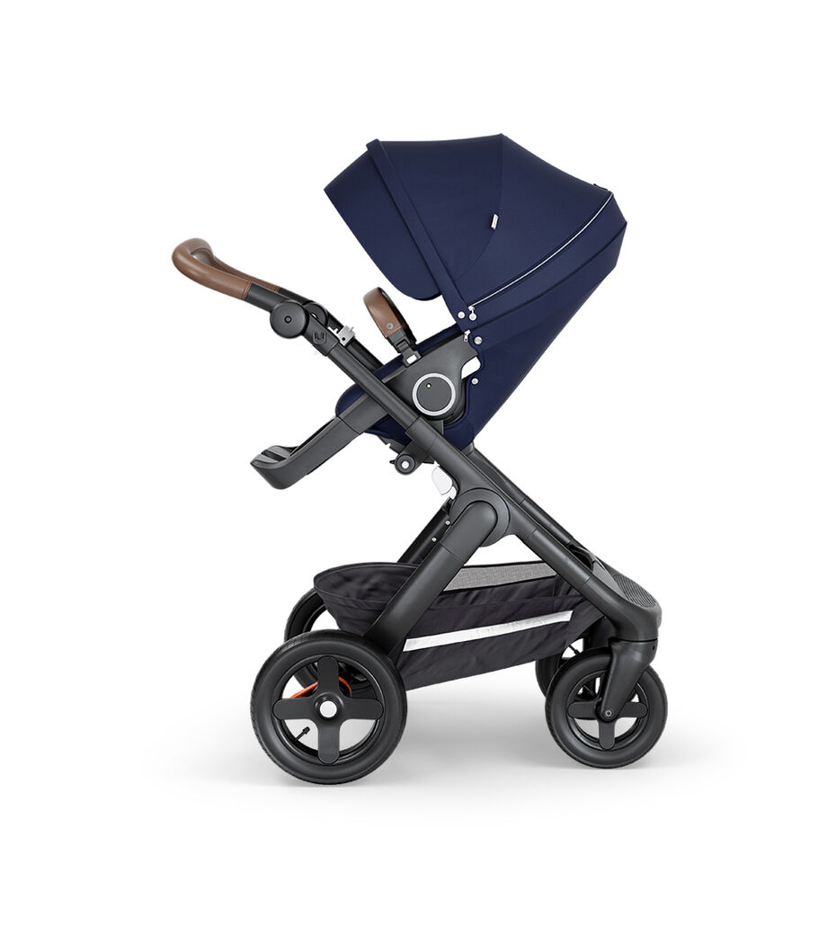 Stokke® Trailz™ with Black Chassis, Brown Leatherette and Terrain Wheels. Stokke® Stroller Seat, Deep Blue.