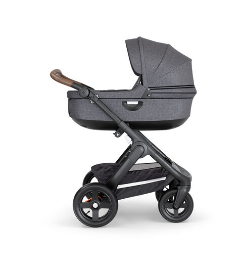 Stokke® Trailz™ with Black Chassis, Brown Leatherette and Terrain Wheels. Stokke® Stroller Carry Cot, Black Melange. view 3