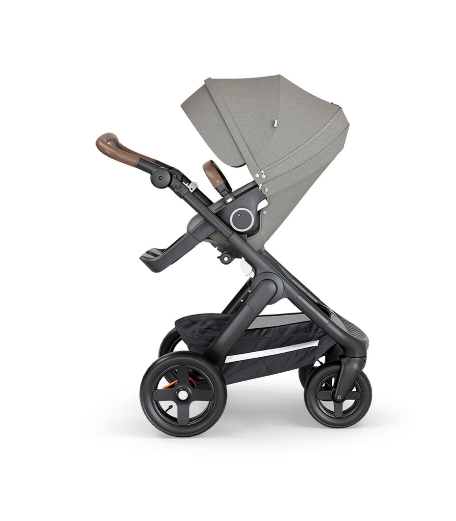 Stokke® Trailz™ with Black Chassis, Brown Leatherette and Terrain Wheels. Stokke® Stroller Seat, Brushed Grey.