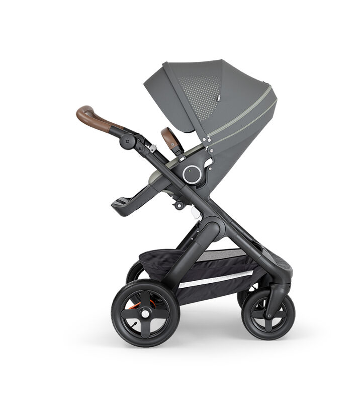 Stokke® Trailz™ with Black Chassis, Brown Leatherette and Terrain Wheels. Stokke® Stroller Seat, Athleisure Green.