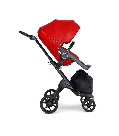 Stokke® Xplory® wtih Black Chassis and Leatherette Black handle. Stokke® Stroller Seat Seat Red. Forward facing.