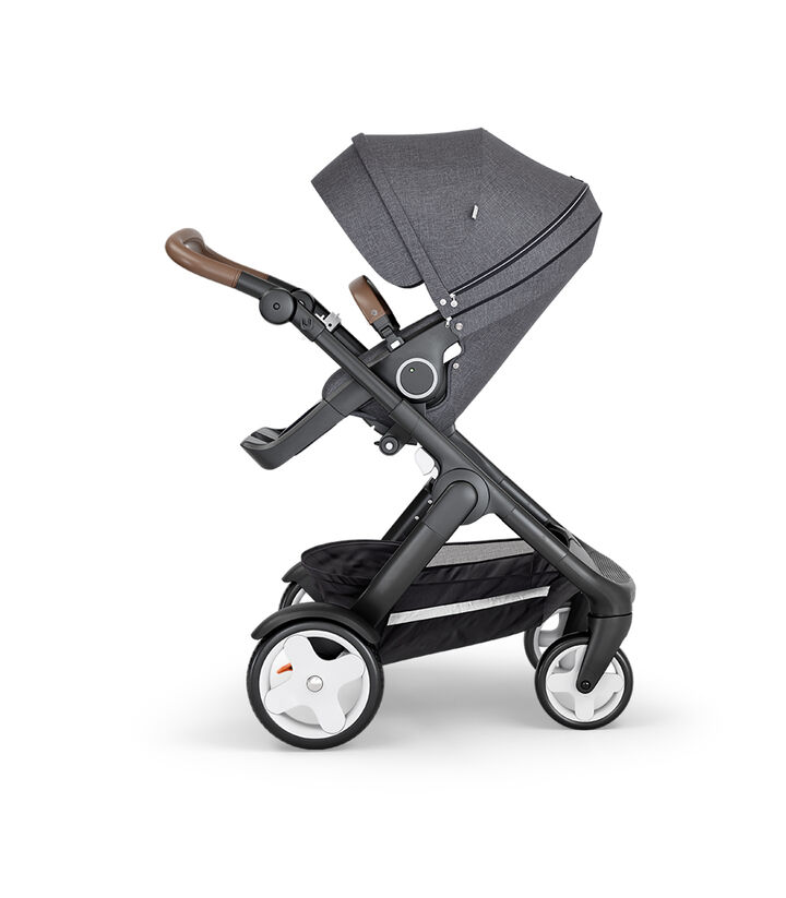 Stokke® Trailz™ with Black Chassis, Brown Leatherette and Classic Wheels. Stokke® Stroller Seat, Black Melange.