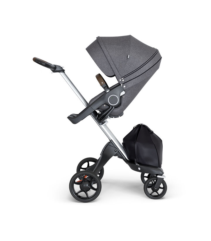 Stokke® Xplory® wtih Silver Chassis and Leatherette Brown handle. Stokke® Stroller Seat Black Melange. view 1
