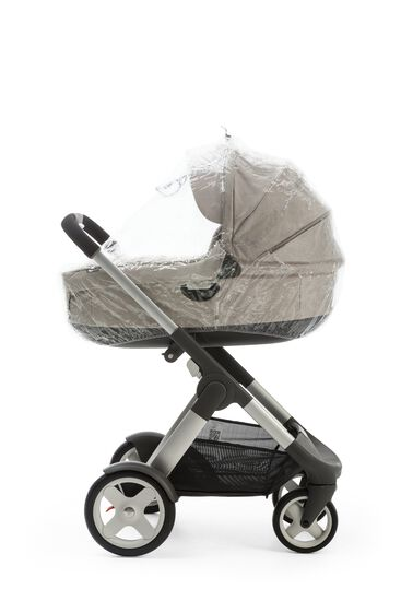 With Stokke® Stroller Carry Cot, Beige. Rain Cover attached.