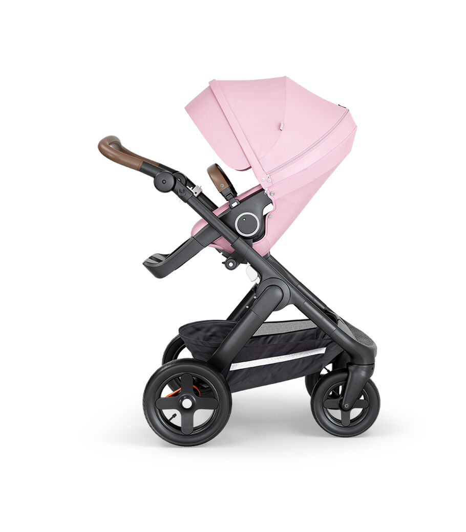 Stokke® Trailz™ with Black Chassis, Brown Leatherette and Terrain Wheels. Stokke® Stroller Seat, Lotus Pink.