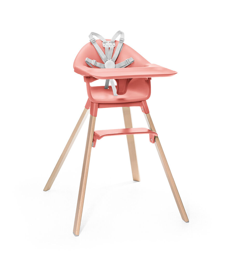 Stokke® Clikk™ High Chair. Natural Beech wood and Sunny Coral plastic parts. Stokke® Harness and Tray attached.