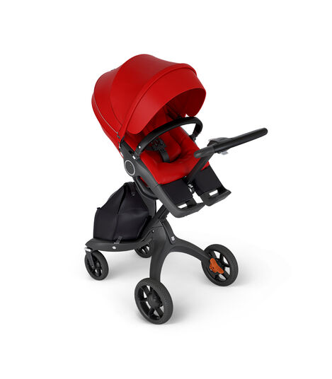 Stokke® Xplory® with Black Chassis and Leatherette Black handle. Stokke® Stroller Seat Red in angled view.