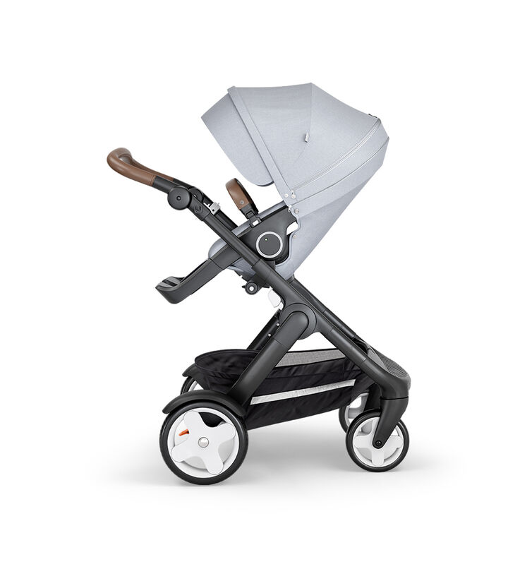 Stokke® Trailz™ with Black Chassis, Brown Leatherette and Classic Wheels. Stokke® Stroller Seat, Grey Melange.