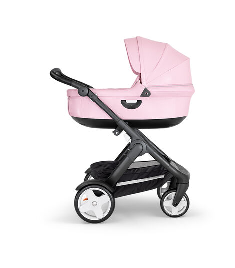 Stokke® Trailz™ with Black Chassis, Black Leatherette and Classic Wheels. Stokke® Stroller Carry Cot, Lotus Pink. view 3