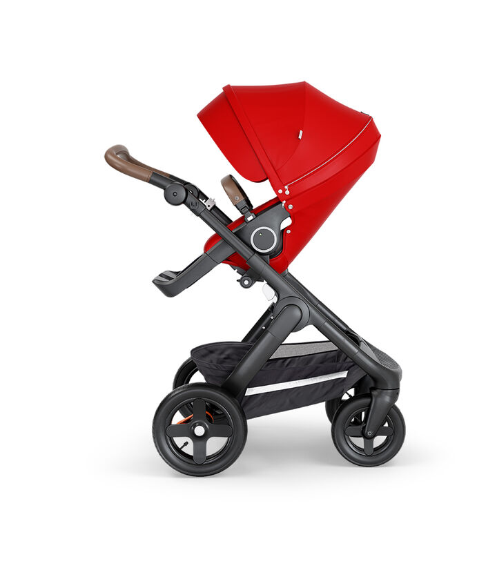 Stokke® Trailz™ with Black Chassis, Brown Leatherette and Terrain Wheels. Stokke® Stroller Seat, Red.