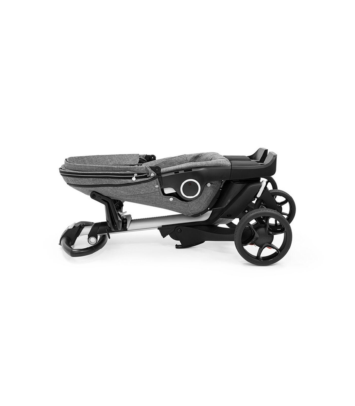 Stokke® Xplory® Silver chassis and  Stokke® Stroller Seat , Black Melange. Folded.