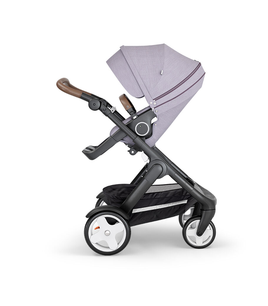 Stokke® Trailz™ with Black Chassis, Brown Leatherette and Classic Wheels. Stokke® Stroller Seat, Brushed Lilac.