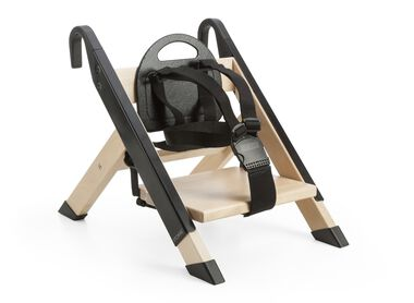 Portable child seat. Black. Accessorised with legs for placing on the floor