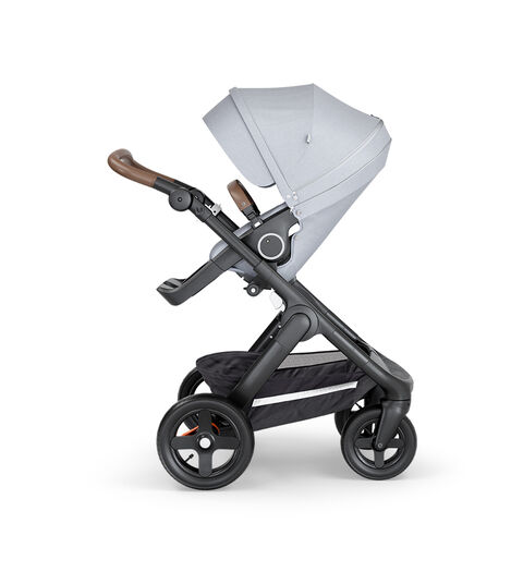 Stokke® Trailz™ with Black Chassis, Brown Leatherette and Terrain Wheels. Stokke® Stroller Seat, Grey Melange.