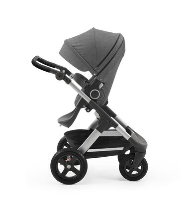 Stokke® Trailz with silver chassis and Stokke® Stroller Seat, parent facing, active position. Black Melange. Terrain wheels. Leatherette Handle.