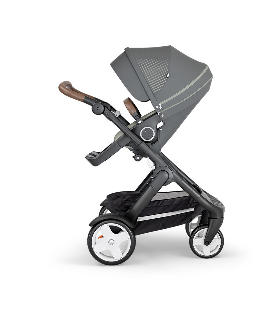 Stokke® Trailz™ with Black Chassis, Brown Leatherette and Classic Wheels. Stokke® Stroller Seat, Athleisure Green.