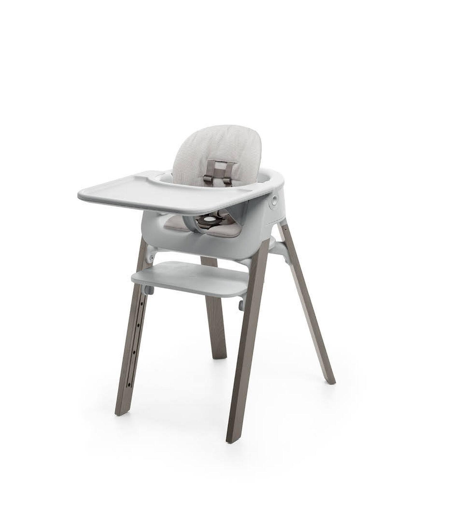 Stokke® Steps™ Hazy Grey with Accessories. Baby Set Light Grey. Baby Set Cushion Timeless Grey. Baby Set Tray Light Grey.