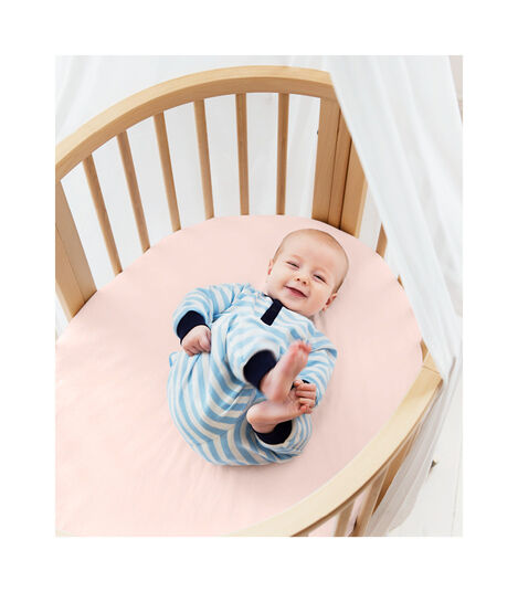 Stokke® Sleepi™ Mini Bed, Natural with Fitted Sheet Peachy Pink.