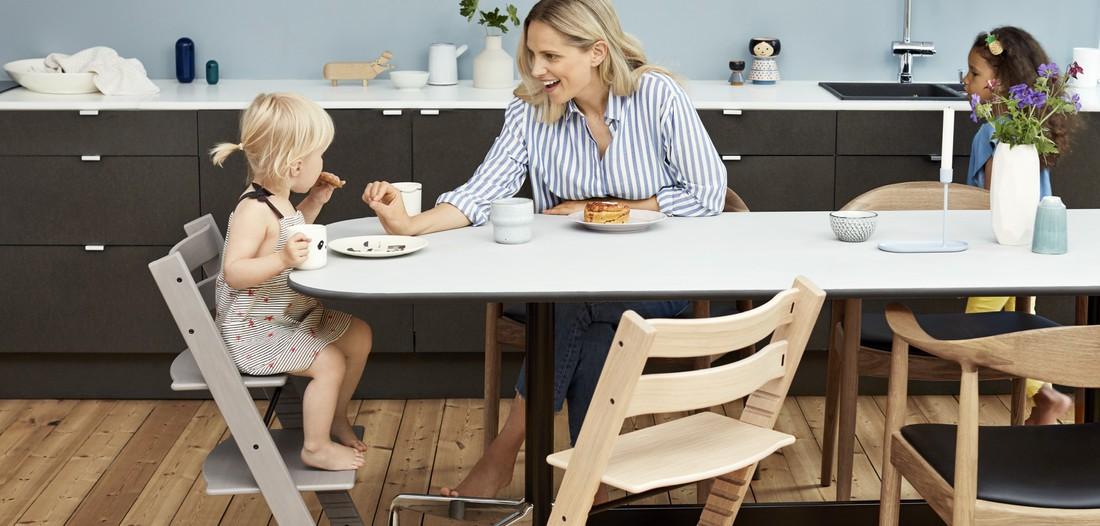 Mamma sitter vid matbordet och äter tillsammans med barnet i en Tripp Trapp-stol