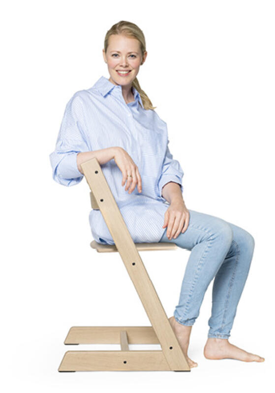 woman sitting on tripp trapp chair