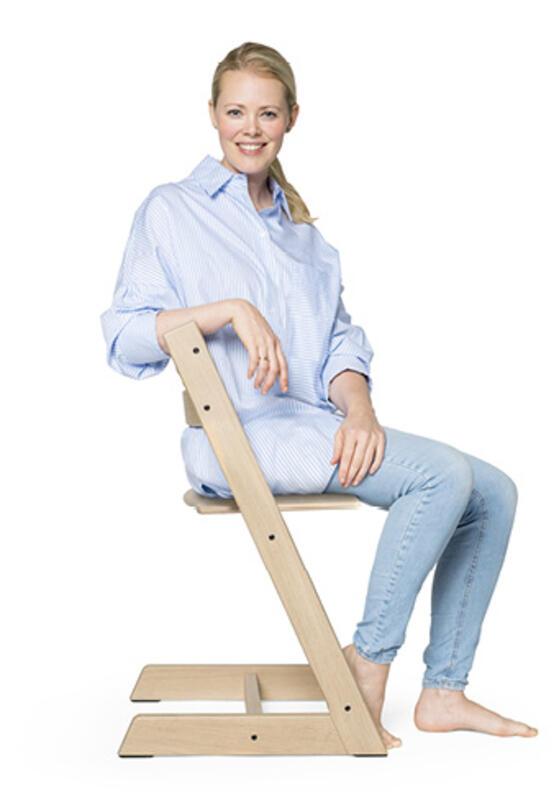 woman sitting on tripp trapp chair