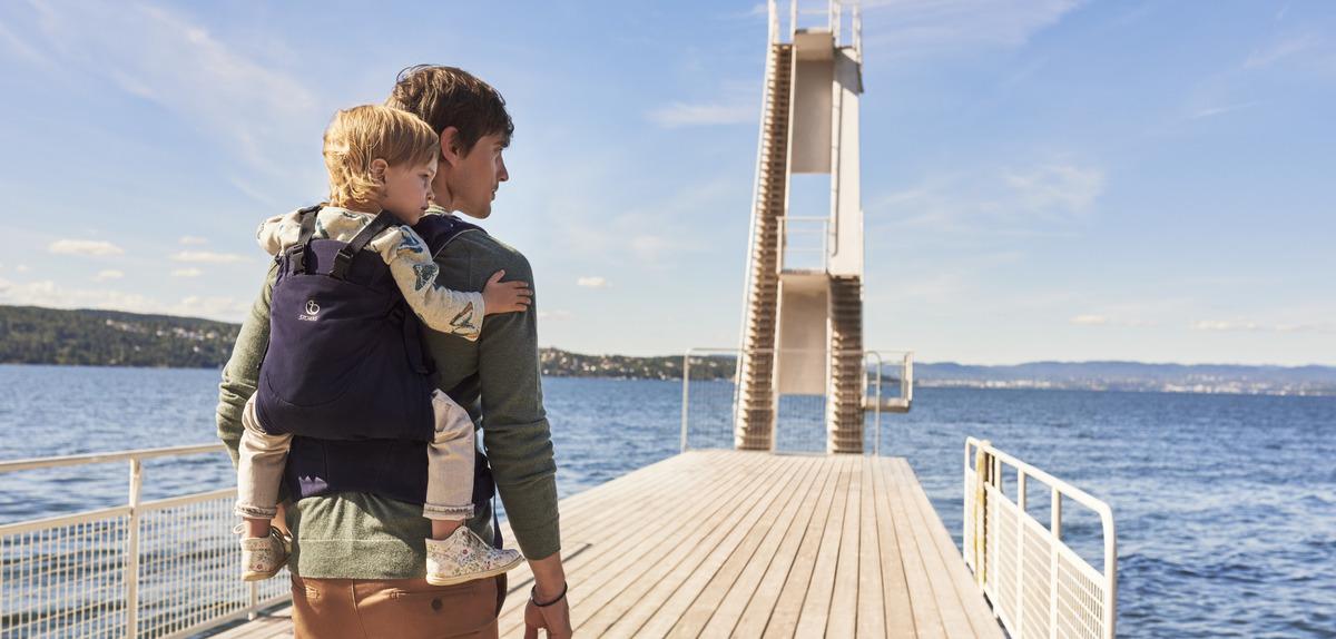 Pappa promenerar längs havet med barnet på ryggen i Stokke MyCarrier