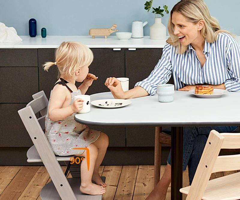 Mother having snacks with her daughter sitting on Tripp Trapp chair