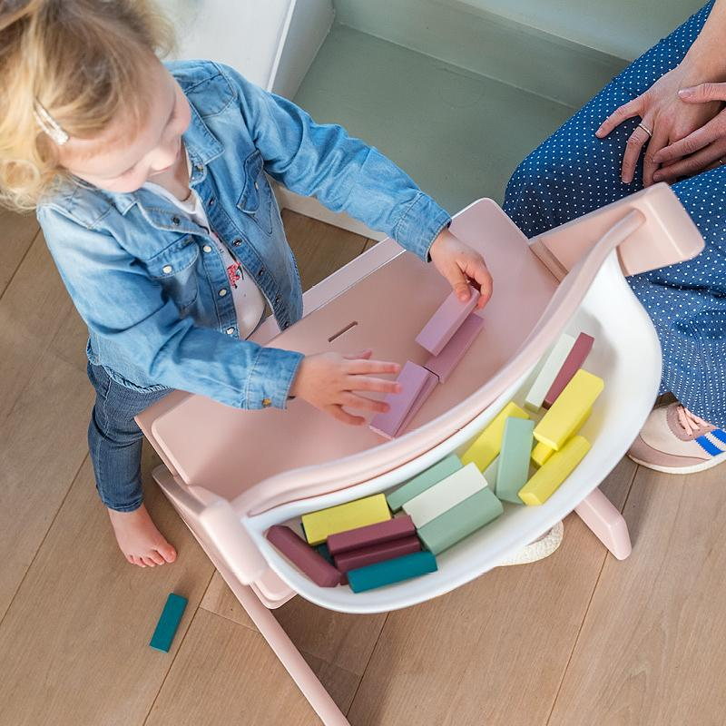 Child playing with bricks at the Tripp Trapp chair with storage