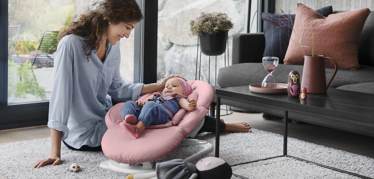 嬰兒躺在 Stokke Steps 多功能嬰童椅搖椅上,媽媽在輕輕搖動