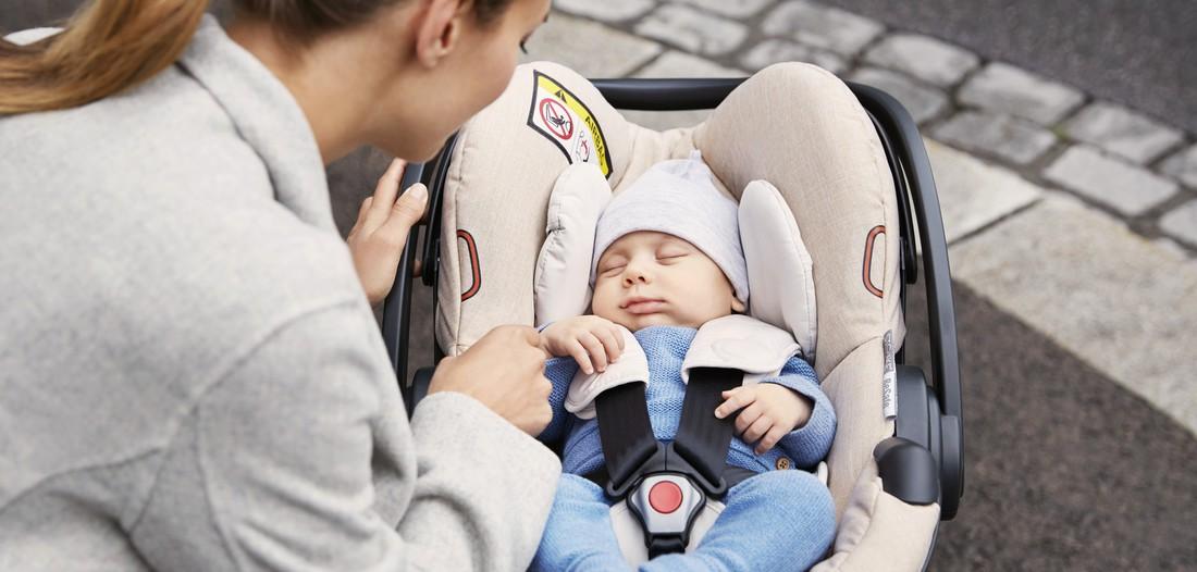 Mor med sin nyfødte i en Stokke iZi Go Modular by BeSafe