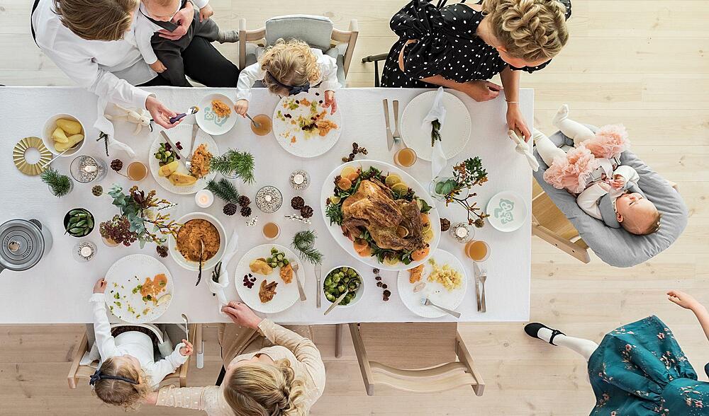 familie sitter rundt et festpyntet bord