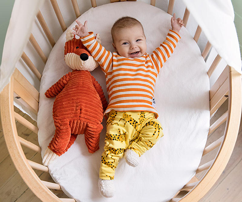 Baby smiling in the Stokke Sleepi bed