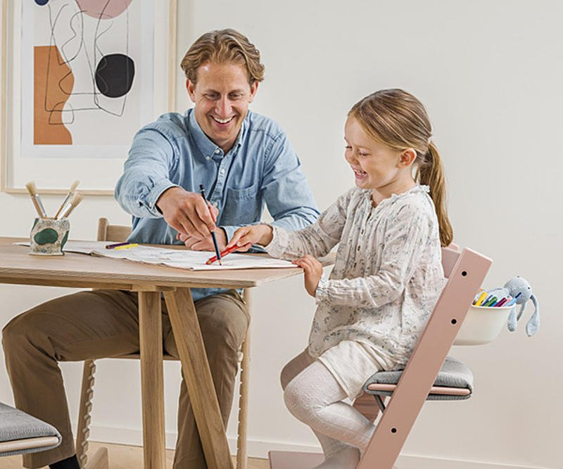 Girl sitting on the Tripp Trapp chair, laughing and painting with her father