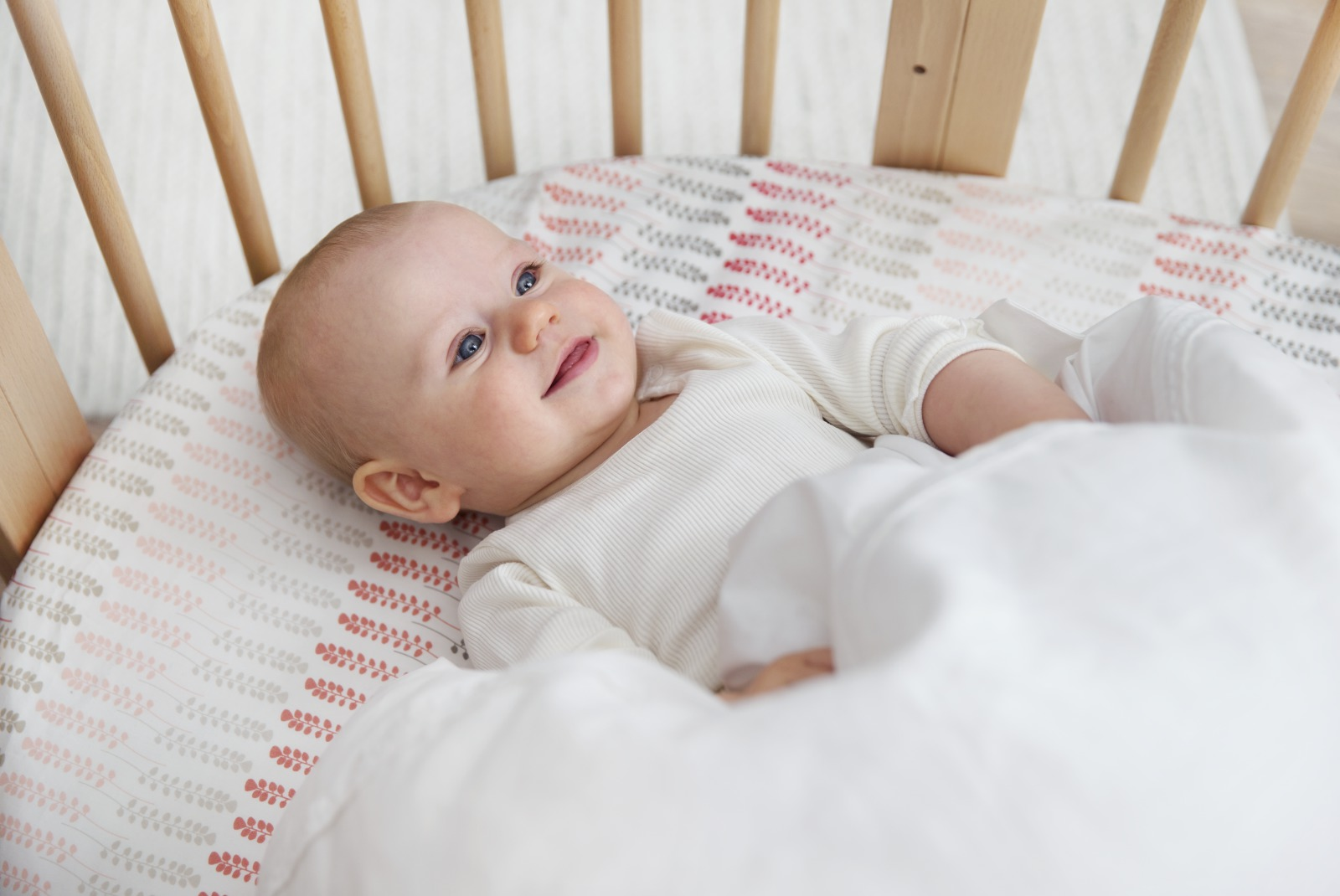Stokke® Sleepi™ Mini, Natural. Fitted Sheet Coral Straw and Bedlinen White.