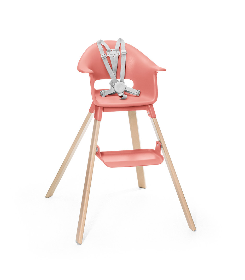 Stokke® Clikk™ High Chair. Natural Beech wood and Sunny Coral plastic parts. Stokke® Harness attached. Footrest high.
