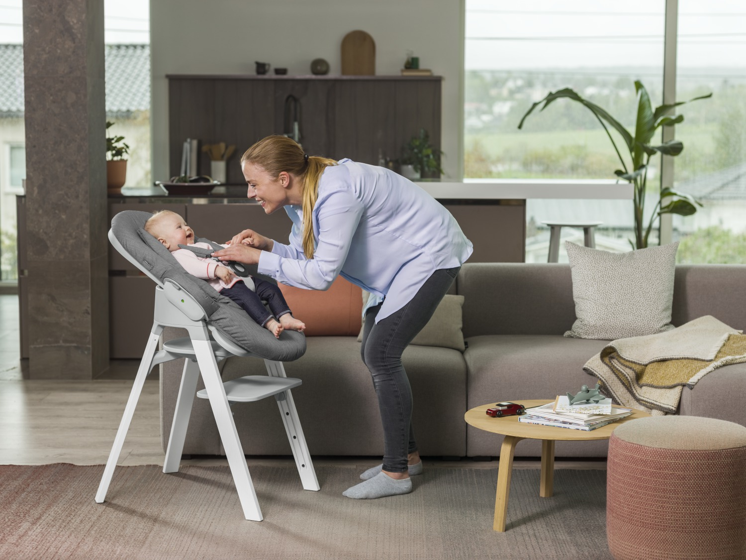 Stokke® Steps™ high chair Oak White with Light Grey seat and Bouncer in Deep Grey textile. On the chair.