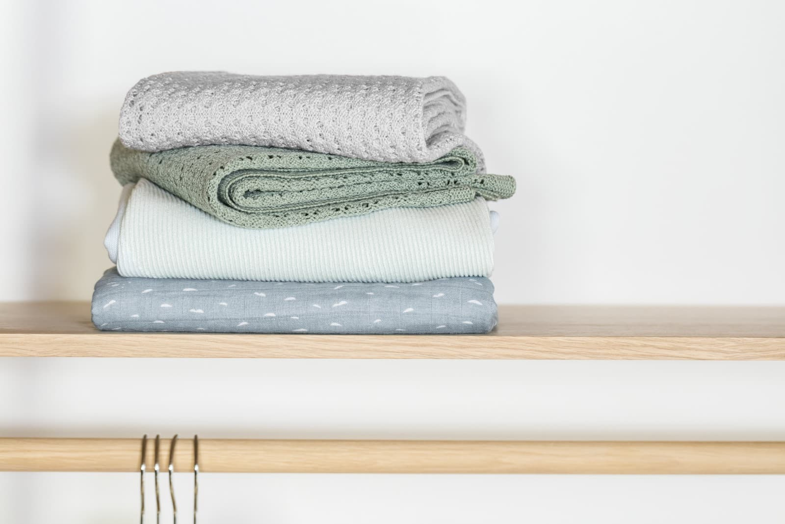 Stokke® Caring Collection. Blanket Merino Wool, Light Grey and Green.   Cotton Knit, Mint. Muslin Cotton, Slate Blue Sea. Indoor.