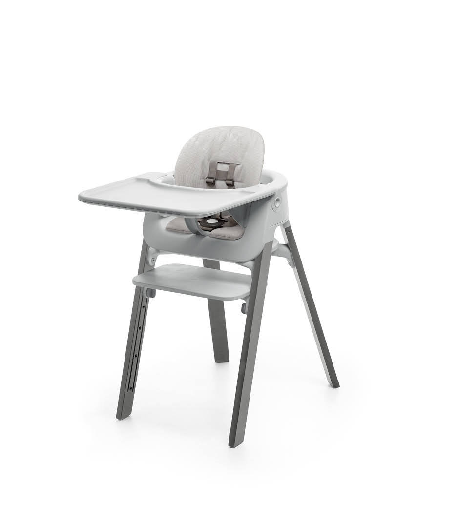 Stokke® Steps™ Storm Grey with Accessories. Baby Set Light Grey. Baby Set Cushion Timeless Grey. Baby Set Tray Light Grey.